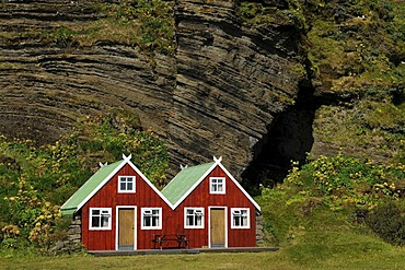 Red holiday homes in front of a rock wall, Vik, South Coast, Iceland, Europe