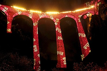"Irrigation water viaduct lit up with the letters 'RhB' to celebrate the acceptance of the ""Rhaetische Bahn Railway in Albula/Bernina"" as a UNESCO World Heritage Site, Filisur, Graubuenden, Switzerland, Europe"