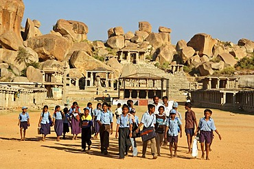 Indian school class in front of temple ruin and granite rocks, Hampi, Karnataka, India, South Asia