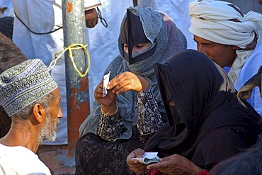Omani women counting money after trading at the goat market, Nizwa, Sultanate of Oman, Middle East