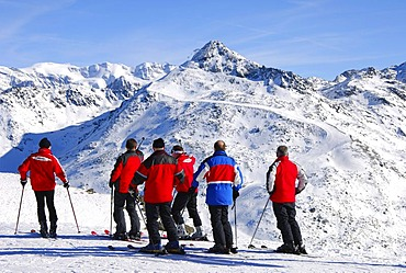 A group of skiers looking down the ski slope at Mont du Vallon, Meribel, skiing area Trois Vallees, France, Europe