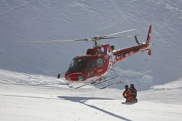 Rescue helicopter taking-off after the rescue of an injured skier on Leukerbad ski piste, Valais, Switzerland, Europe