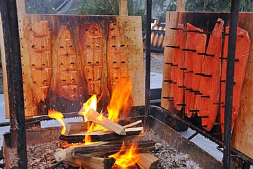 Salmon being smoked over open fire, Finnish Christmas market in Stuttgart, Baden-Wuerttemberg, Germany