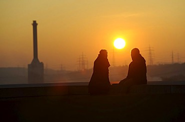 Two people in the forefront of EnBW Energiepark at sunset, Marbach on the Neckar, Baden-Wuerttemberg, Germany, Europe
