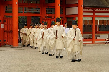 Shinto priests at archery opening ceremonial in Shimogamo Shrine, striding through entrance gate, Kyoto, Japan, Asia