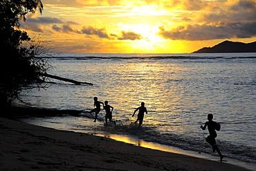 Children playing by the sea at sunset, Anse La Reunion, La Digue, Seychelles