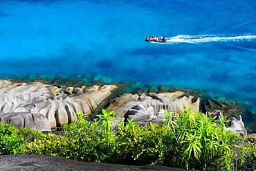 Granite rocks and tropical vegetation in front of a boat on the sea, northwest coast, Mahe, Seychelles