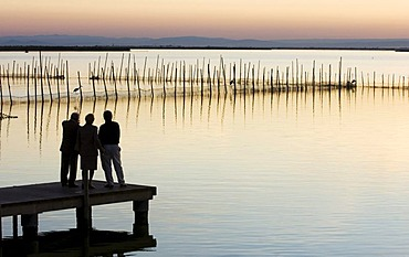 Two men and a woman on a pier, Lake Albufera at sunset, south of Valencia, Spain, Europe