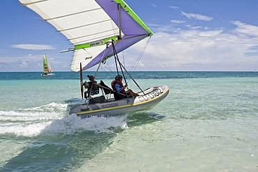 Motorised hang glider landing on the sea, UL-Trike, Ultra Light airplane with a life boat, Varadero, Cuba, Caribbean, Central America, America