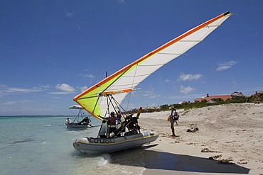 Pilot of a motorised hang glider waiting for passengers on a beach, UL-Trike, Ultra Light airplane with a life boat, Varadero, Cuba, Caribbean, Central America, America
