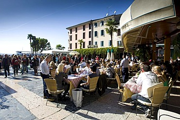 Tourists sitting in a restaurant on the promenade of Sirmione, Lake Garda, Lago di Garda, Lombardy, Italy, Europe