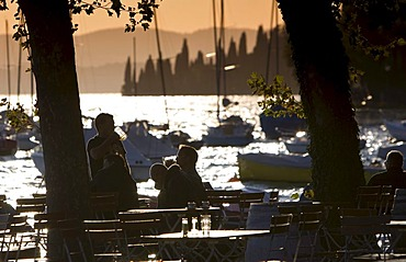 Tourists sitting in a restaurant at sunset on the shores of Lake Garda, Lago di Garda, Lombardy, Italy, Europe