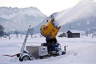 Snow cannon spraying snow into a valley between Ehrwald and Lermoos at dusk, Tyrol, Austria, Europe