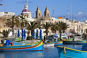 Traditional Maltese fishing boats, called Luzzu, in front of the Church of Our Lady of Pompeii, port of Marsaxlokk, Malta, Europe