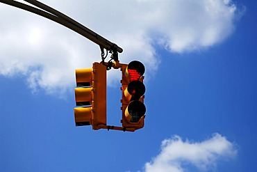 Yellow traffic light in front of blue sky in Newton, New Jersey, USA