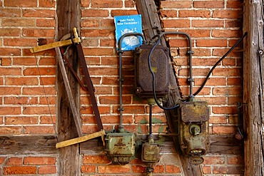 Old connection box and a handsaw on a timber-framed wall, Neso, Mecklenburg Western-Pomerania, Germany, Europe