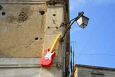 Street lamp, red electric guitar on the facade of the Max Bar in the historic centre of Tropea, Vibo Valentia, Calabria, South Italy, Europe