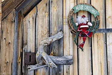 Christmas wreath decoration on wilderness lodge door in Saariselkae skiing region, Ivalo, Lapland, Finland, Europe