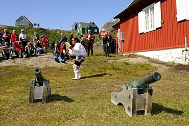 Inuit wearing a traditional costume, folklore in front of a museum in Tasiilaq, Ammassalik, East Greenland, Greenland