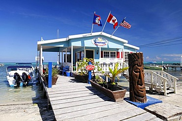 Carved wooden face in front of a restaurant on a pier in the ocean of San Pedro, Ambergris Cay Island, Belize, Central America, Caribbean