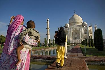 Women wearing saris walking towards the mausoleum of the Taj Mahal, Agra, Uttar Pradesh, North India, India, Asia