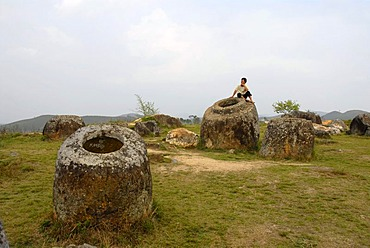 A person sitting on one of the mysterious bellarmines, Plain of Jars, place of discovery No. 1 (Thong Hai Hin), Xieng Khuang Province, Laos, South East Asia