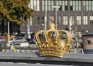 Golden Swedish crown on the handrail of the bridge between the two islands Blasieholmen and Skeppsholmen, Stockholm, Sweden, Scandinavia, Europe