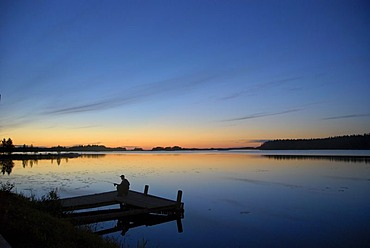 Fisher on a jetty in evening light, Saimaa Lake District, Finland, Europe