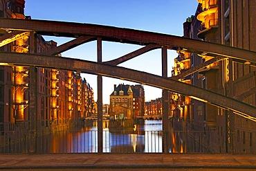 View through Poggenmuehlenbruecke bridge towards Wasserschloesschen, water castle, in Speicherstadt, old warehouse district, in evening light, port of Hamburg, Hamburg, Germany, Europe