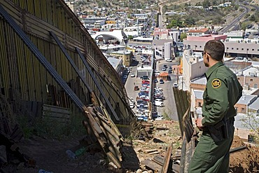A US Border Patrol agent stands by the border fence that separates the United States and Mexico, Nogales, Arizona, USA