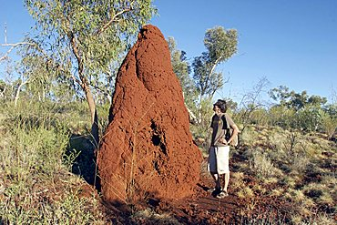 man stays next to a termite hill Karijini National Park Pilbara region western australia WA