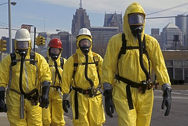 During a training session for workers dealing with toxic chemical spills, participants in protective suits walk down the street, Detroit, Michigan, USA