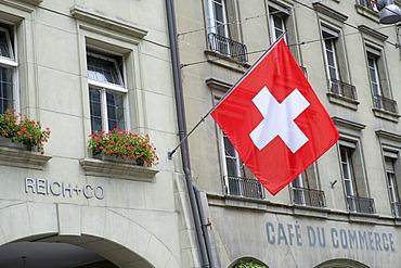 Swiss flag hanging from a building facade, Bern, Switzerland, Europe
