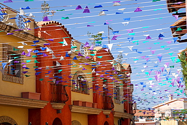 Street with many colourful flags, Pula, Sardinia, Italy
