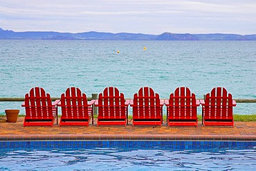 Red deckchairs with view of the ocean, swimming pool in the foreground