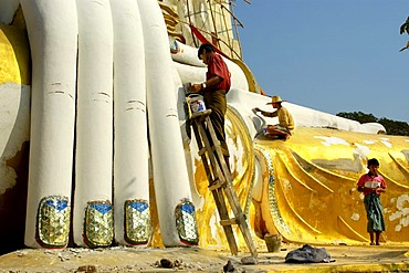 Renovation in progress painter paints the hand of big sitting Buddha Kyaikpun Bago Burma