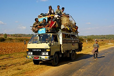 Many men and luggage pile up on the roof of a small Toyota lorry near Pindaya Shan State Burma