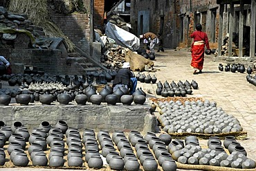 Potter working among many pots put out for drying on Potters' Square Bhaktapur Nepal