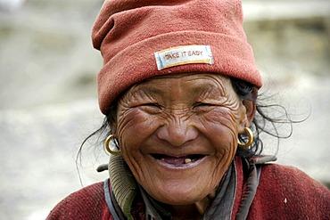 Portrait old woman wearing a fleece cap with sign Take It Easy Phu Nar-Phu Annapurna Region Nepal