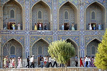 Young women dancing in arches of Madrasah Tilla-kari Registan Samarkand Uzbekistan