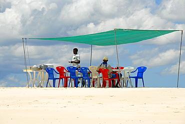 Table and chairs in the shade for lunch on a white sand bank near Kizimkazi Zanzibar Tanzania