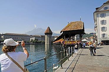 Tourists taking pictures, Kapellbruecke, Chapel Bridge, water tower, Reuss River, historic district, Lucerne, Switzerland, Europe
