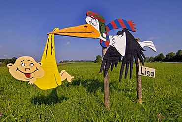 Wooden sign of a stork in a field, newborn baby, Upper Bavaria, Germany