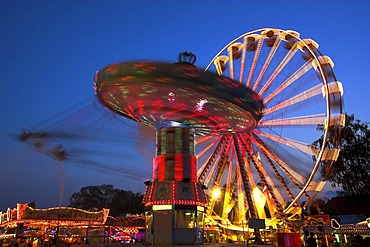 Amusement park during blue hour with Merry-Go-Round and big wheel in movement