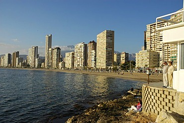 Tourists looking out on the beach of Benidorm, Playa de Levante, Costa Blanca, Spain