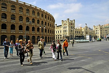 People crossing the street on a zebra crossing in front of a bullfight arena and the main station, Valencia, Spain