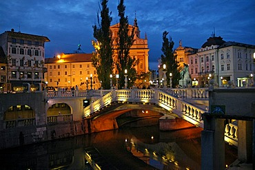 The triple bridge or three bridges crossing the river Ljubljanica to the Preseren square, and the Franciscan church in the back, Ljubljana, Slovenia