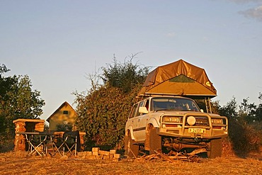 Toyota Land Cruiser 4x4 with tent loaded onto its roof at a campsite in Ihaha, Chobe National Park, Botswana, Africa