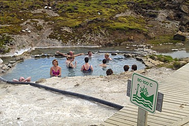 A relaxing bath in the 40 centigrade warm waters of the hot spring in Hveravellir the sign is related to another hot spring Iceland