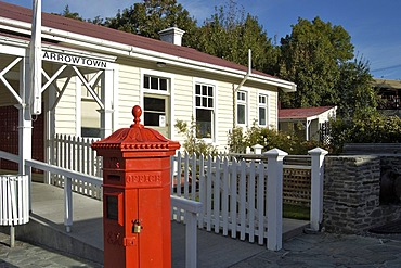 Red letter box and an old historical building of the former gold rush town, Arrowtown, South Island, New Zealand